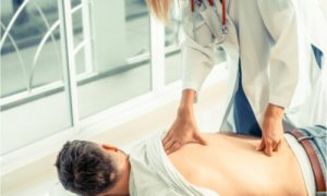 The chiropractor massages the patient's back.