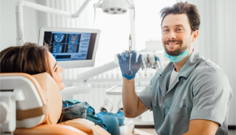 The dentist holds the syringe to inject an anesthetic into the patient.